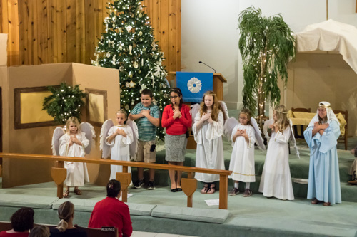 Children crossing their hearts, singing carols